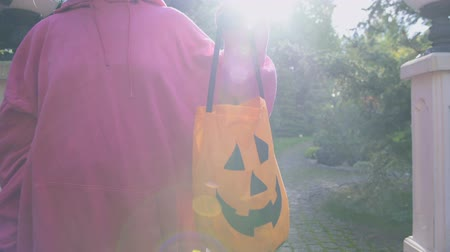 этап : Woman holding Trick or Treat bag, asking for sweets at Halloween party entrance