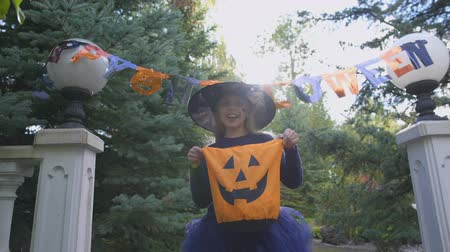 treating : Little witch holds Trick or Treat bag, asks for sweets outdoors, Halloween party