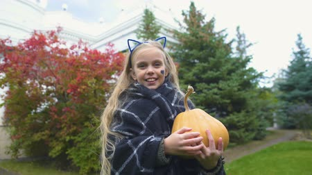 spojrzenie : Cheerful girl shows thumb up, holds Jack pumpkin for Halloween, autumn holiday