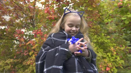 finomságok : Overjoyed girl holding candies and dancing outdoors, enjoying Halloween holiday