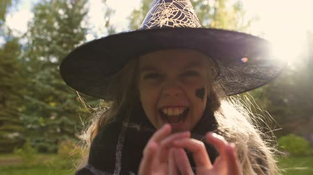 fobi : Girl playing evil witch, angrily roaring at camera, Halloween party celebration