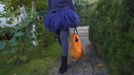 finomságok : Little girl with trick or treat bag walking to neighbors for candies, Halloween Stock mozgókép
