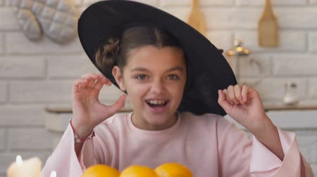 questão : Girl making scary face in witch costume jumping from under table Halloween party Stock Footage