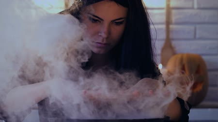 superstition : Beautiful woman in witch costume making magic potion, preparing for Halloween