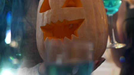 carving : Young people having Halloween party, holding pumpkin, drinking alcohol together