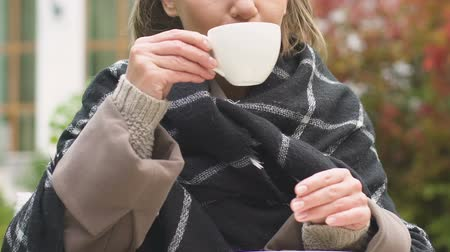 mulled wine : Woman having cup of cocoa sitting on garden terrace, warming up on cold fall day