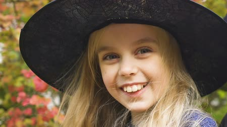 vampiro : Funny smiling little girl in witch hat posing at camera, Halloween party outfit