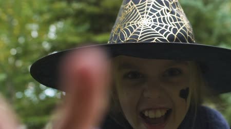 witch hat : Cute little girl in witch outfit making scary faces camera, pretending conjure