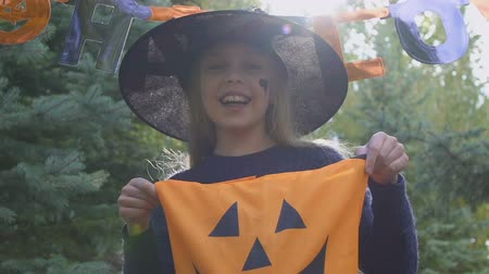treating : Smiling girl holding trick or treat bag, Halloween game preparation.