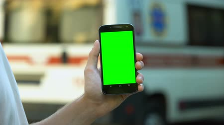 paramedics : Patient holding phone, ambulance on background, site with online medical advices Stock Footage