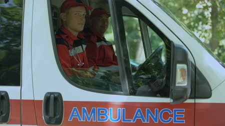 fidedigno : Friendly doctors in ambulance looking at camera, professional emergency service
