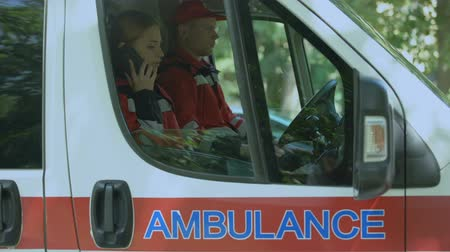 экипаж : Female paramedic using smartphone to call patient, ambulance crew on-duty
