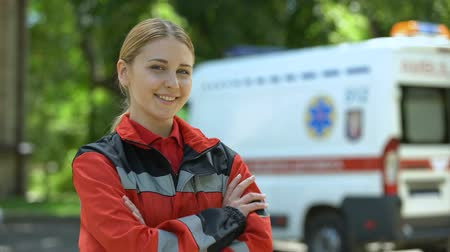 fidedigno : Friendly female paramedic posing for camera, ambulance on background.