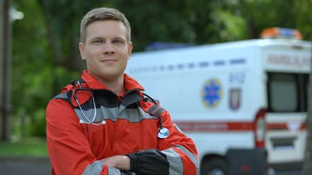 экипаж : Male paramedic posing for camera, ambulance on background, professionalism