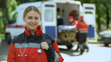 ambulância : Paramedic posing for camera, ambulance crew transporting patient to clinic