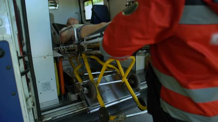 paramedics : Paramedics carrying patient on stretcher into ambulance, fast qualified help Stock Footage
