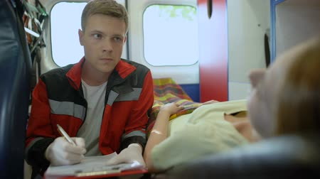 жертва : Doctor asking patient questions and filling out medical form in ambulance