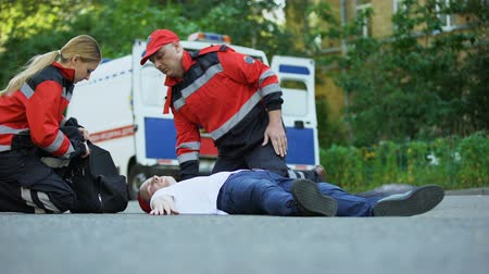 reanimation : Ambulance crew running to man lying on road, first aid at car accident scene