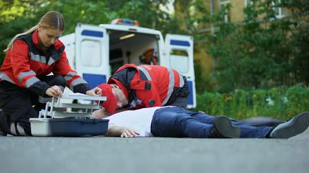 glicose : Paramedics helping unconscious man lying on road, making injection with insulin Stock Footage