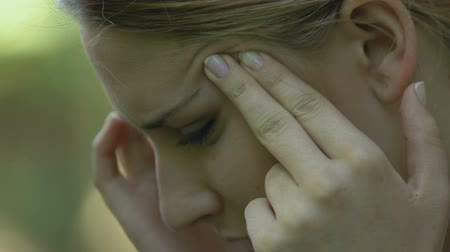 chronic : Beautiful young female suffering from terrible migraine, massaging temples Stock Footage