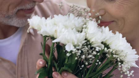 gentleman : Old man presenting woman with bouquet of flowers, happy senior couple close up