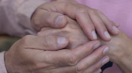 saygı : Elderly man carefully touching womans wrinkled hands, support and care, close up Stok Video