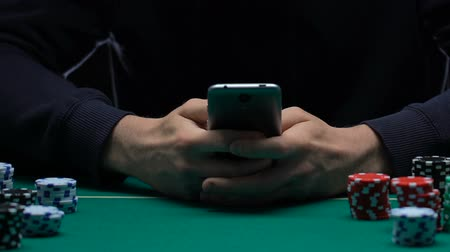 umutlu : Man playing poker on his smartphone, plunged into casino atmosphere. Stok Video