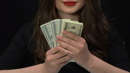 prémie : Female speculator showing dollars earned on frauds with bank accounts.