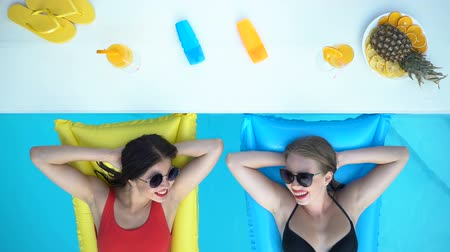 talk : Two women laughing in swimming pool top view, enjoying summer holidays at resort
