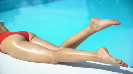 nogi : Sexy woman legs with clean shaved soft skin near swimming pool, summer suntan
