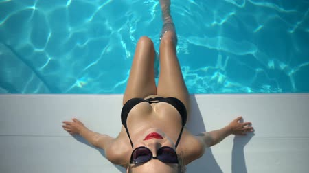 plavat : Tanned sporty woman relaxing in swimming pool, slim lady enjoying summer