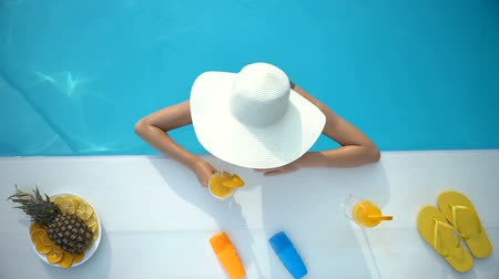 топ : Young woman in hat chilling in swimming pool with tropical cocktail, vacation Стоковые видеозаписи