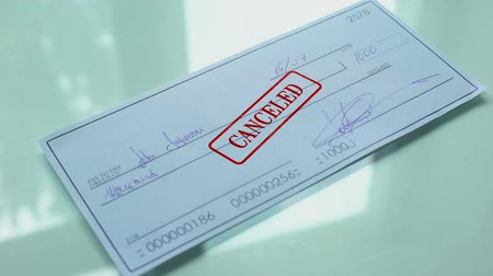 cheated : Cheque document canceled, hand stamps seal on official paper, insufficient funds Stock Footage