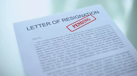 očekával : Letter of resignation document pending, hand stamping seal on official paper