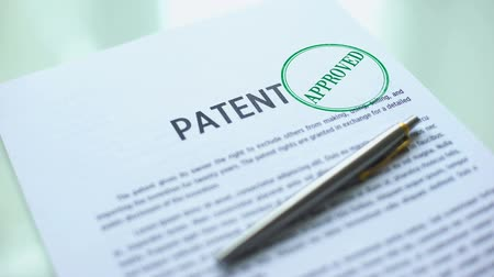 belgeleme : Patent document approved, hand stamping seal on official paper, copyright law Stok Video