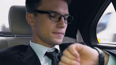 nervous : Young businessman nervously looking at watch while sitting on back seat of car Stock Footage