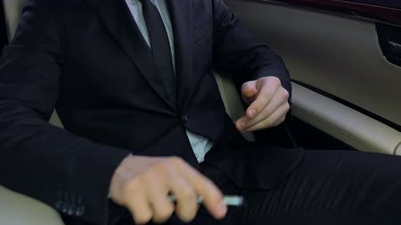 nervous : Irritated businessman holding phone, sitting in car and banging fist on knee