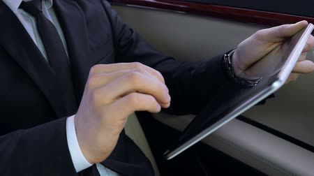 billionaire : Young successful businessman sitting in luxury car, working on tablet, hard work