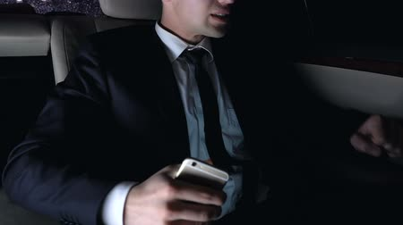 formální : Disappointed man sitting on back seat of car and using smart phone