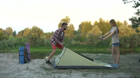 кемпинг : Couple putting up dome tent, wilderness survival training, essential skills