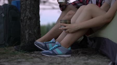 tentáculo : Hikers in sport shoes sitting in tent, drinking tea, resting after busy day Stock Footage