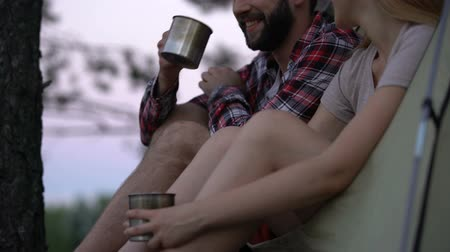 remembering : Couple talking and drinking tea in tent, remembering funny moments, camping