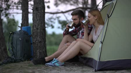 tentáculo : Young couple sitting in tent drinking tea and talking, escape from city life Stock Footage