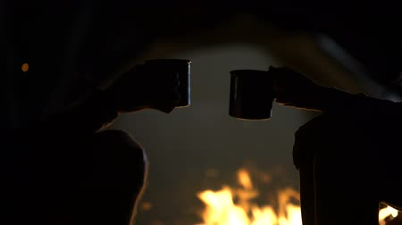 javasol : Iron cups with drinks against bonfire and tent, clinking together, close up