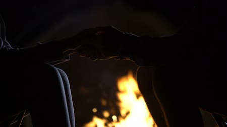 söz : Man holding girlfriends hand against bonfire, romantic love confession.