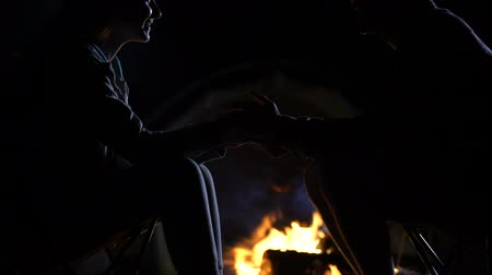 harcerz : Silhouette of male holding girlfriends hands, telling scary story near bonfire Wideo
