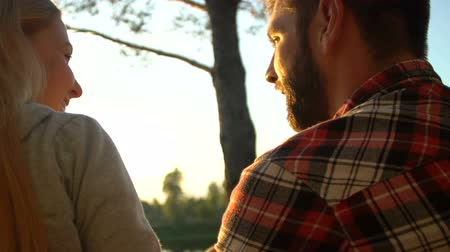camping : Bearded man and woman hugging and enjoying cool sunset at riverside, back view