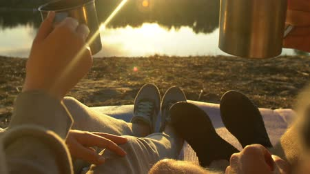 teacup : Couple sitting near lake, clinking tea cups and enjoying beautiful sunset, relax