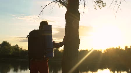 zálesí : Young male backpacker enjoying sunset near lake, trekking in forest, traveling