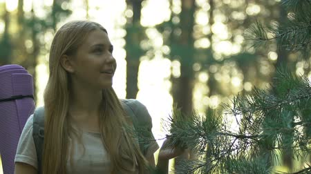 harcerz : Young blond hiker enjoying forest beauty and smiling, trekking in woodland alone